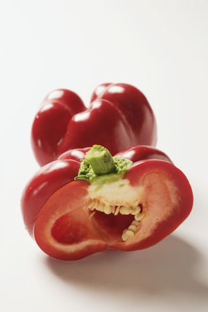 cut off: Two red peppers, one with a piece cut off