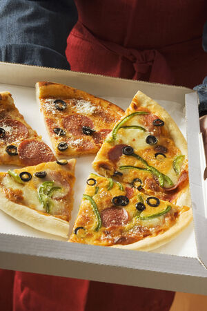 pizza box: Pieces of different pizzas in pizza box