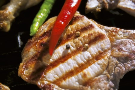 pork chop: Grilled pork chop with pepper and chili peppers LANG_EVOIMAGES