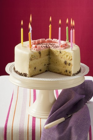 ignited: Birthday cake with burning candles, pieces taken