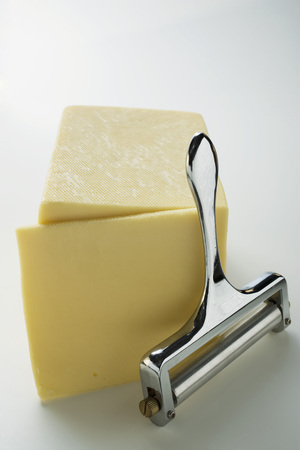 parer: Semi-hard cheese with a slice cut and a cheese cutter