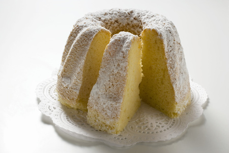 doiley: Ring cake with icing sugar, a piece cut, on doily