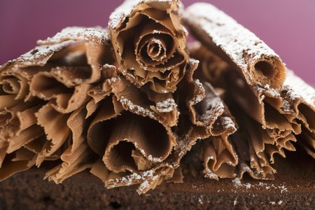 chocolate curls: Chocolate curls with icing sugar on chocolate cake