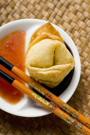 hoisin sauce: A deep-fried wonton with two sauces (close-up)