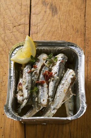 european anchovy: Fried anchovies with dried tomatoes in aluminium dish