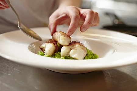 plating: A chef arranging fish in bacon on a plate LANG_EVOIMAGES