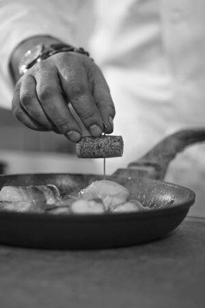fish dish: A chef preparing a fish dish (black-and-white image)