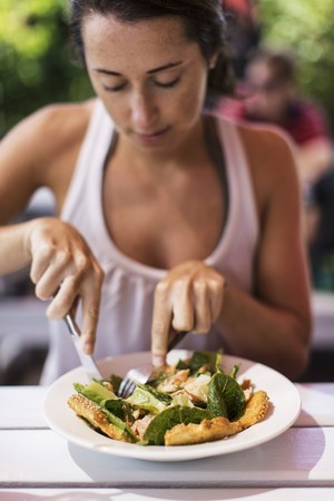 provenance: A woman eating a salmon salad in a garden restaurant LANG_EVOIMAGES