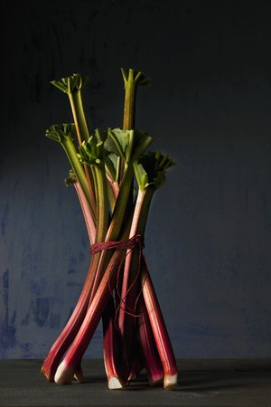 redness: A bunch of rhubarb on a wooden surface against a blue background