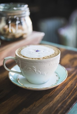 lavandula angustifolia: Cafe latte with milk foam and a lavender flower LANG_EVOIMAGES