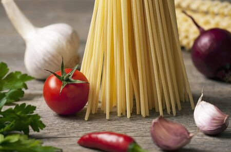 petroselinum sativum: An arrangement of pasta, vegetables and parsley on a wooden table