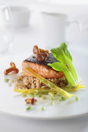 salmon fillet: Salmon fillet with chanterelle mushrooms on a bed of barley