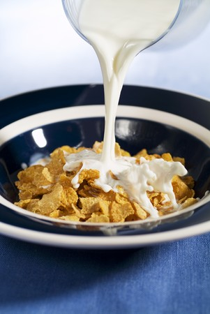 cornflakes: Milk being poured over cornflakes