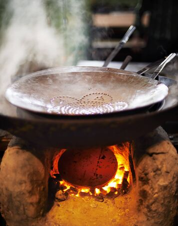 A steaming pan of oil on a traditional clay stove LANG_EVOIMAGES