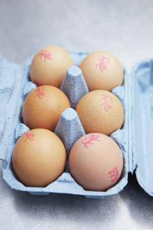 brownness: Six brown eggs with stamps in an egg box LANG_EVOIMAGES