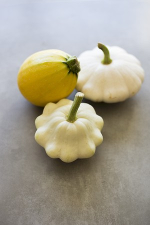 space for type: Two white patty pan squashes and a yellow summer squash on a grey surface