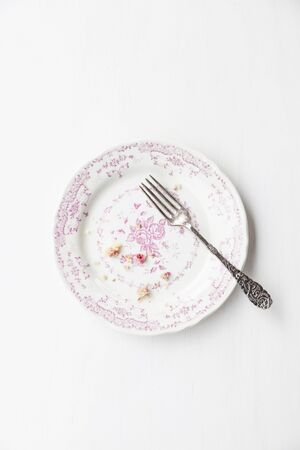 leftovers: Muffin crumbs and a fork on a vintage plate LANG_EVOIMAGES