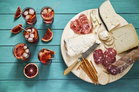 nibbles: An Italian appetiser platter next to glasses of aperitifs garnished with slices of blood orange