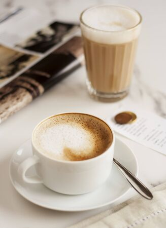 hot coffees: A cappucino and a caffe latte next to a magazine LANG_EVOIMAGES