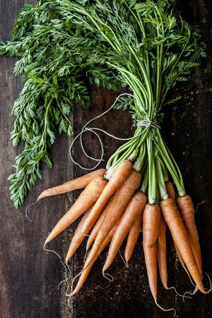 bunched: A bunch of carrots on a wooden surface