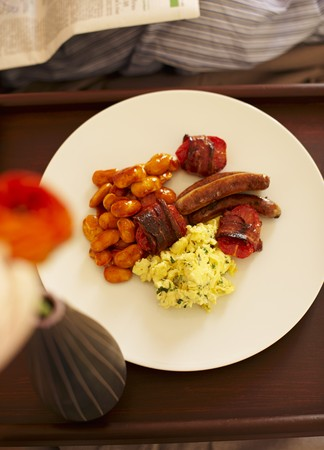 bacon baked beans: An English breakfast with scrambled eggs, baked beans, tomatoes, bacon and sausages