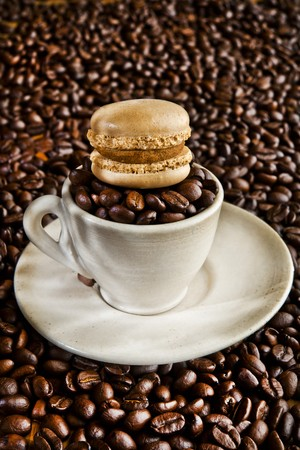 coffeebeans: A mocha macaroon on top of a cup filled with coffee beans LANG_EVOIMAGES