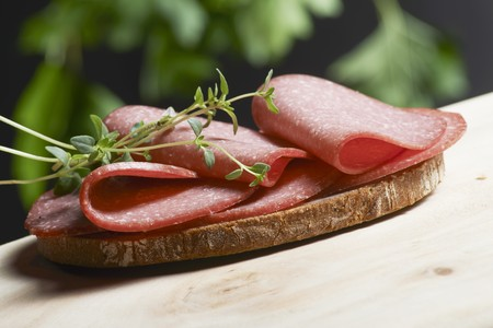 wild marjoram: A slice of bread topped with salami and fresh oregano on a wooden table in a garden LANG_EVOIMAGES