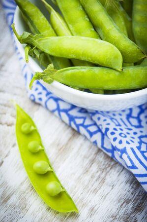 tout: A bowl of fresh mange tout, one pod opened