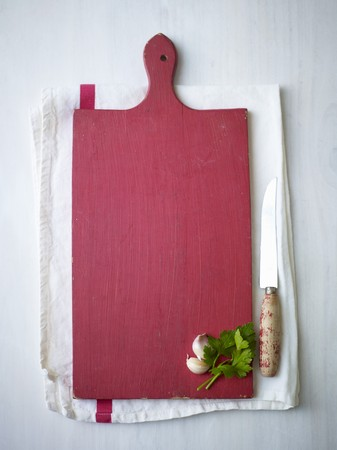 petroselinum sativum: Garlic and parsley on a red wooden chopping board on a tea towel next to a knife