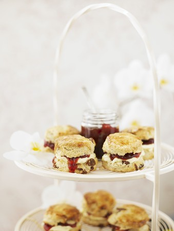 a jar stand: Scones with cream and strawberry jam on a white metal cake stand LANG_EVOIMAGES