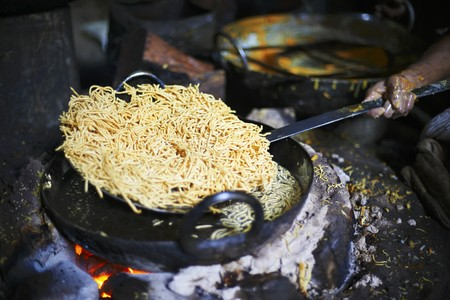 smeared hand: Omapodi being removed from hot oil (chickpea and rice flour snack, India) LANG_EVOIMAGES
