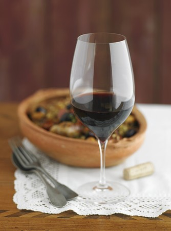 brownness: A glass of red wine with tapas in a terracotta bowl in the background LANG_EVOIMAGES