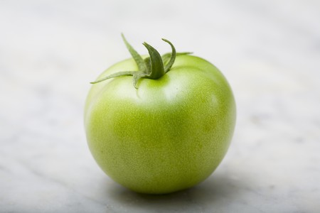 one item: A green tomato on a marble platter