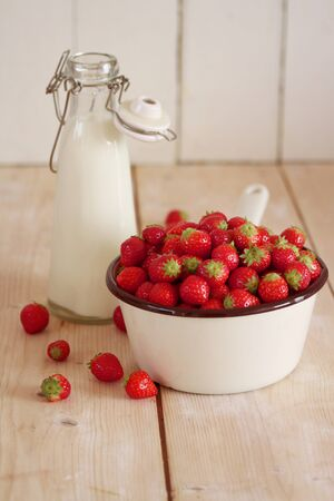 fragaria: Strawberries in a saucepan next to a milk bottle LANG_EVOIMAGES