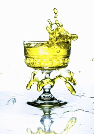 squirted: A yellow drink splashing from a glass