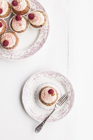buttercream: Raspberry and almond muffins decorated with buttercream and dried raspberry powder