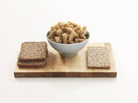 several breads: Wholemeal bread, wholemeal pasta and wholemeal crispbread on a wooden board LANG_EVOIMAGES