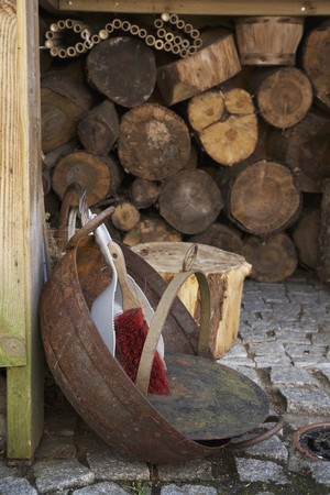 woodshed: A dustpan and brush in a rusty bowl on cobbles in front of a wood shed