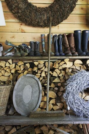 woodshed: An old broom between a tray and a woven wreath on a wooden bench in front of a wood pile with a shelf of rubber boots above it LANG_EVOIMAGES