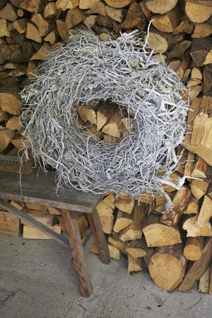 log basket: A woven wreath on a bench against a wood pile