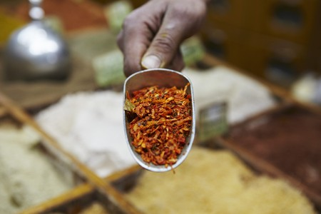 provenance: A hand holding a scoop of kabseh spice mix at a market