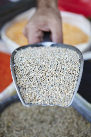 provenance: A hand holding a scoop of bulgar wheat at a market stall