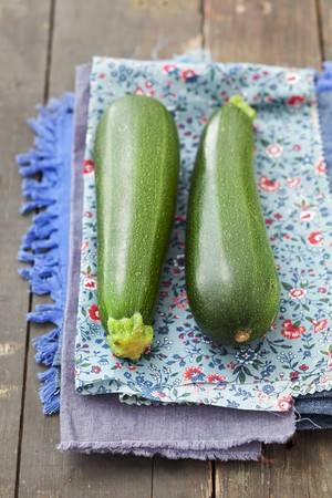 cocozelle: Two courgettes on a floral-patterned cloth