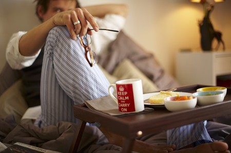 uk cuisine: A man eating an English breakfast in bed