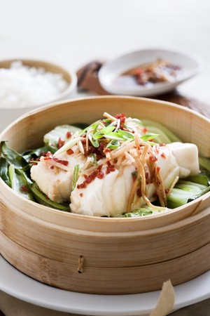 close up of onions in a basket: Steamed fish on a bed of bok choy with ginger and chilli