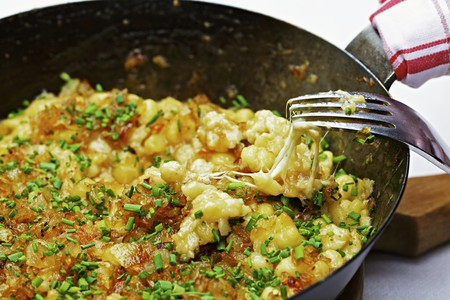 Cheese Spätzle (soft egg noodles from Swabia) with chives in a pan