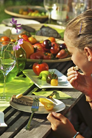 provenance: A girl eating tomatoes at a garden table in the summer LANG_EVOIMAGES