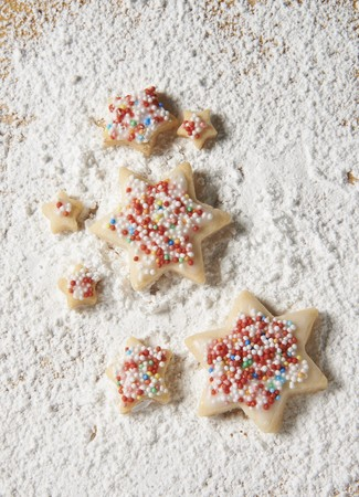 dragees: Star biscuits with coloured sprinkles on a sugared wooden board