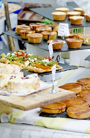 uk cuisine: A market stand selling baked goods featuring syrup cakes and vegetable pizzas (England)