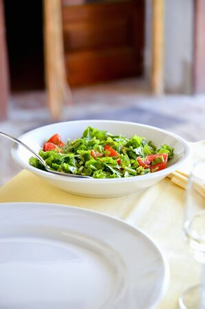arugola: Chopped rocket and tomato salad on a table in a restaurant (Italy)